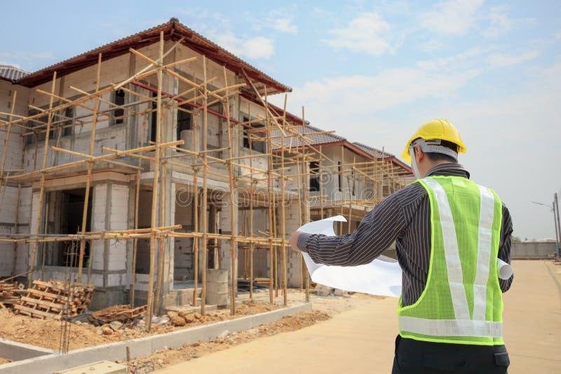 Yrkesmässig teknikerarkitektarbetare med skyddande hjälm- och ritningpapper på platsen för husbyggnadskonstruktion arkivfoto