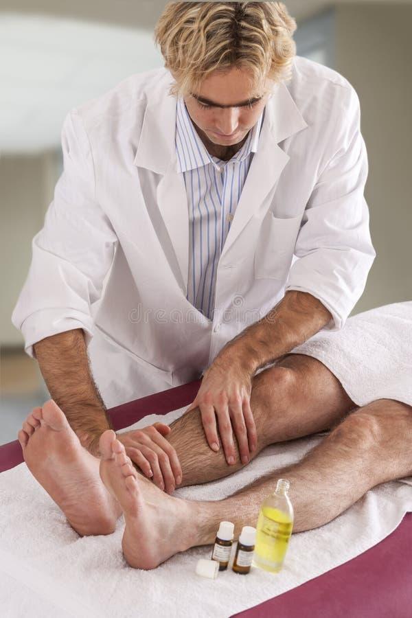 Yrkesmässig terapeut som ger avslappnande reflexology thailändsk fotmassage till en kvinna i brunnsort arkivfoton