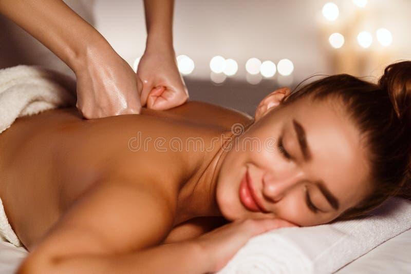 Yrkesmässig terapeut som tillbaka gör massage till kvinnan royaltyfri foto