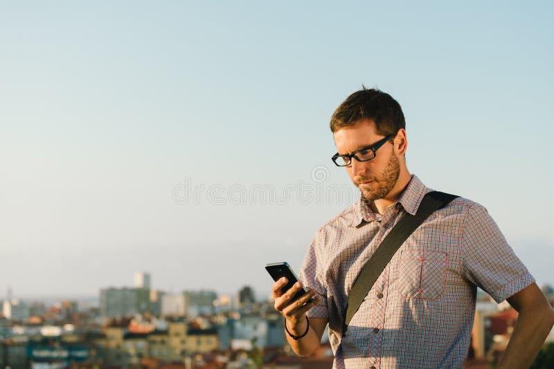 Yrkesmässig tillfällig man som kontrollerar meddelanden på smartphonen arkivfoto