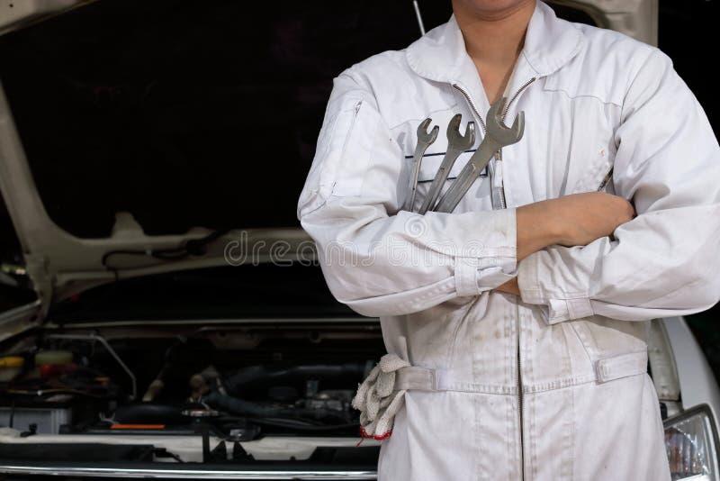 Yrkesmässig ung asiatisk mekanikerman i enhetlig innehavskiftnyckel mot bilen i öppen huv på reparationsgaraget royaltyfri foto