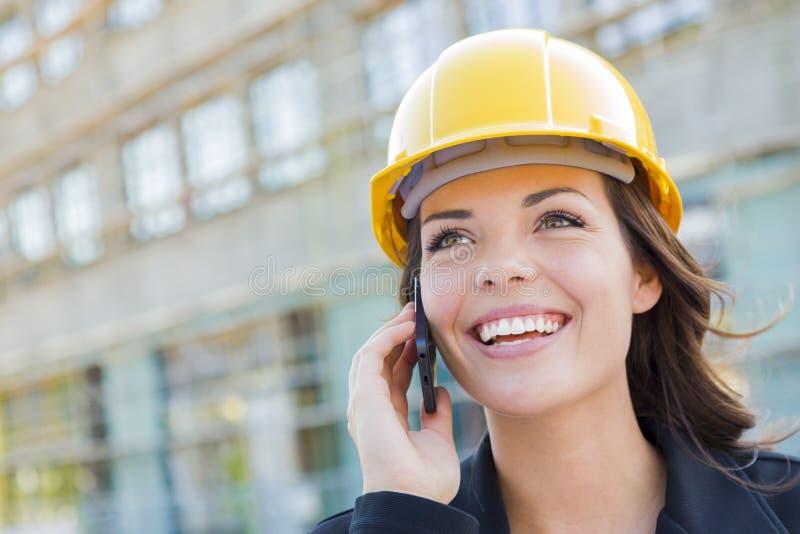 Yrkesmässig ung kvinnlig leverantör som bär den hårda hatten på plats genom att använda telefonen royaltyfria bilder