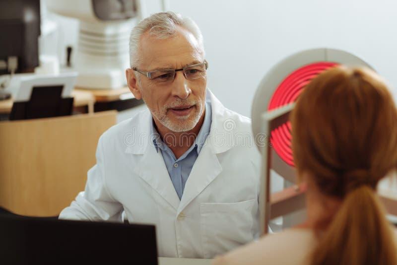Yrkesmässig upptagen ögonläkarekänsla, medan undersöka patienten royaltyfria bilder