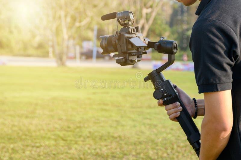 Yrkesmässig videographer med kameran på gimbalstabilisatorn för att ta arkivbild