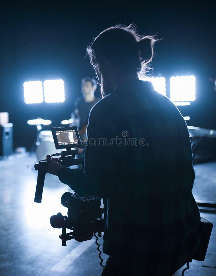 Yrkesmässig videographer som rymmer kameran på gimbal för 3 axel Videographer genom att använda steadicam Pro-utrustning hjälper  arkivfoto