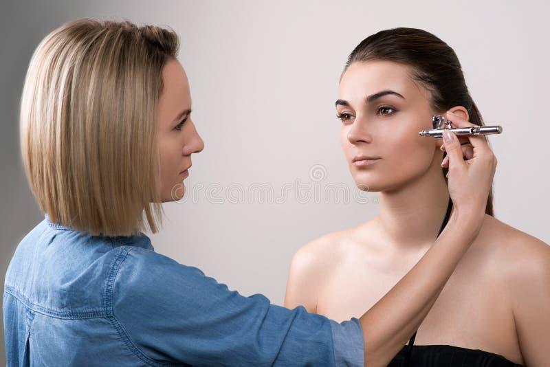 Yrkesmässig visagist som gör makeup och använder retuschsprutan Flicka som gör makeup i skönhetsalong Modebrunettmodell med hårsv fotografering för bildbyråer
