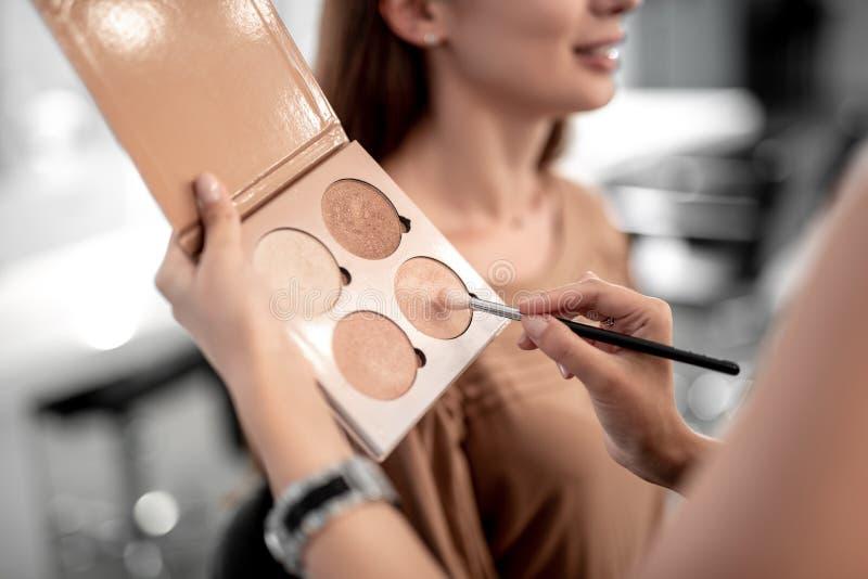 Yrkesmässig visagiste gör makeup för att le kvinnan arkivbild