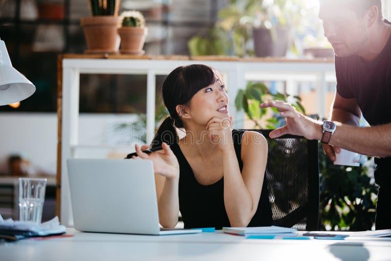 Yrkesmässiga anställda som diskuterar idéer av projektet på bärbara datorn fotografering för bildbyråer