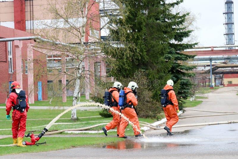Yrkesmässiga brandmän i orange fireresistant dräkter i vita hjälmar med gasmaskar testar brandslangar och brandvapen till e arkivfoton