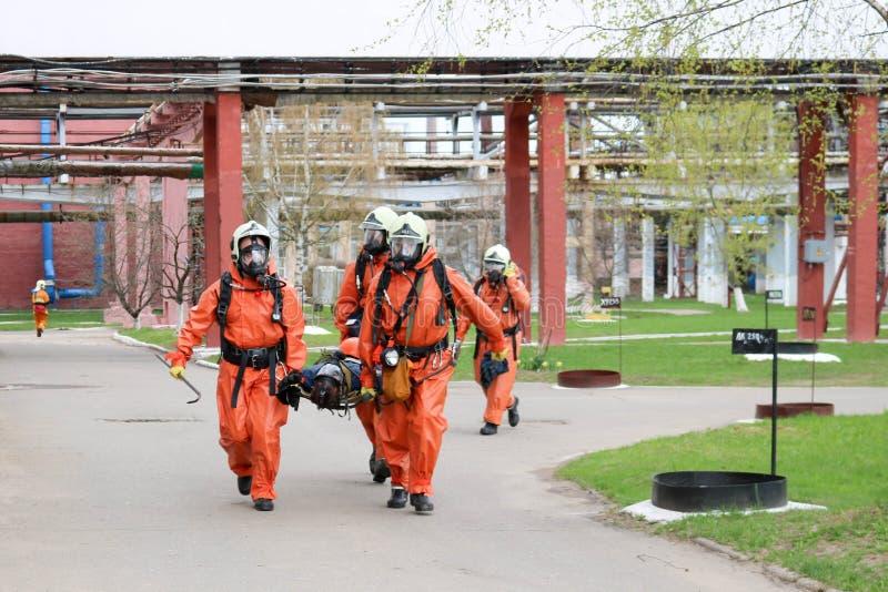 Yrkesmässiga brandmanräddare i orange skyddande fireresistant dräkter, vita hjälmar och gasmaskar uthärdar den sårade personen arkivbilder