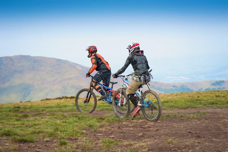 Yrkesmässiga cyklister som rider den sluttande mountainbiket på bergslingan royaltyfri bild