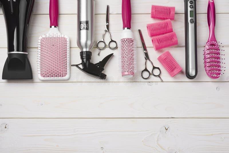 Yrkesmässiga frisörhjälpmedel på träplankabakgrund med kopieringsutrymme royaltyfri fotografi