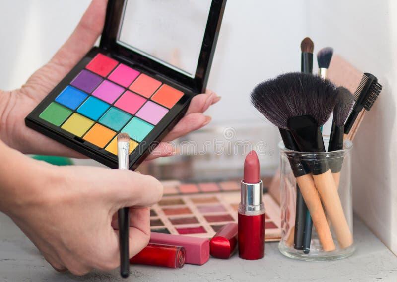Yrkesmässiga kosmetiska borstar, skuggor, läppstift och svampar på en grå tabell arkivfoton