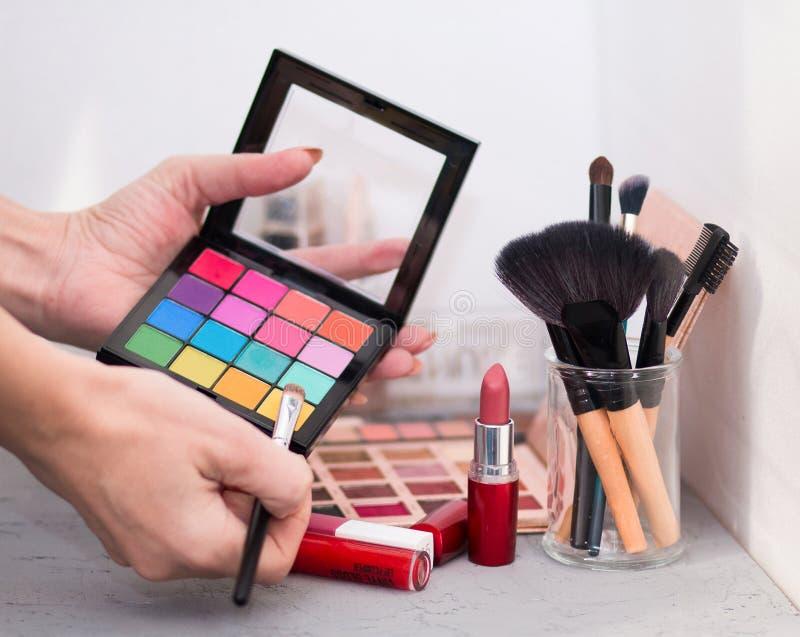 Yrkesmässiga kosmetiska borstar, skuggor, läppstift och svampar på en grå tabell royaltyfria bilder