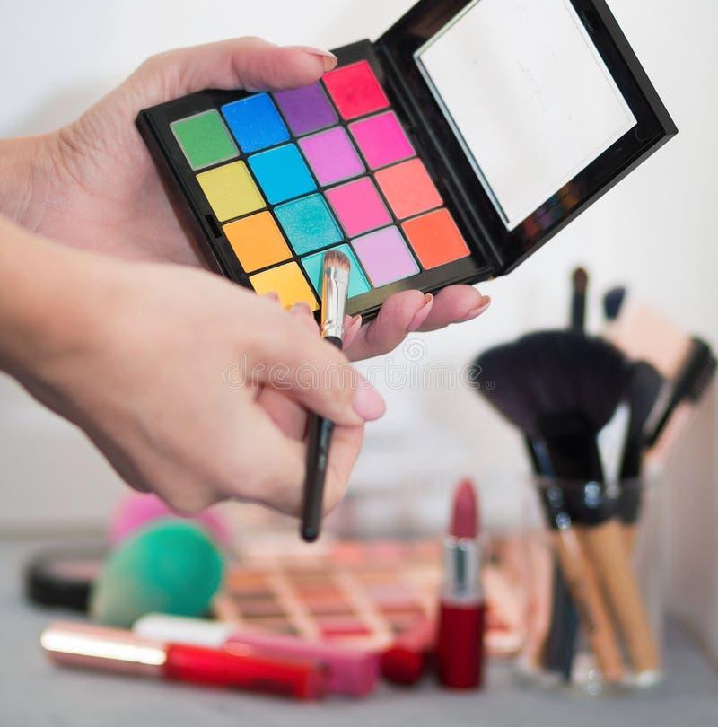 Yrkesmässiga kosmetiska borstar, skuggor, läppstift och svampar på en grå tabell royaltyfri fotografi