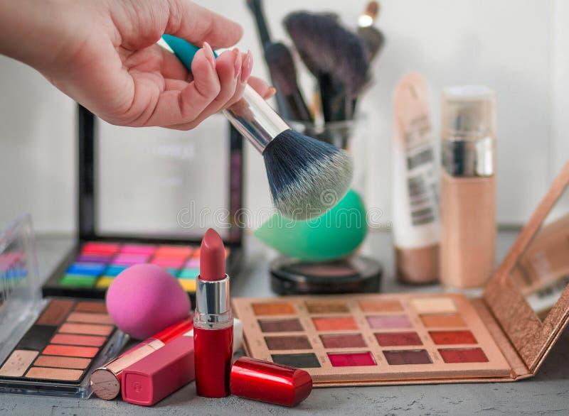 Yrkesmässiga kosmetiska borstar, skuggor, läppstift och svampar på en grå tabell royaltyfri foto