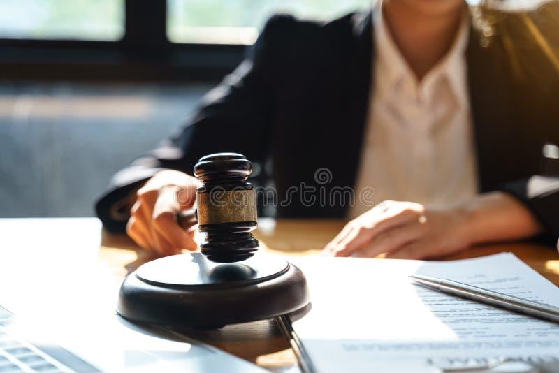 Yrkesmässiga kvinnliga advokater som arbetar på advokatbyråerna med domareauktionsklubban på trätabellen Begrepp av lag fotografering för bildbyråer