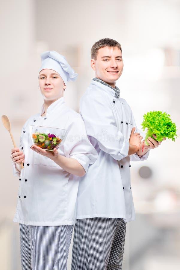 yrkesmässiga lyckliga kockar i dräkter med en sallad i deras händer mot bakgrunden royaltyfri fotografi