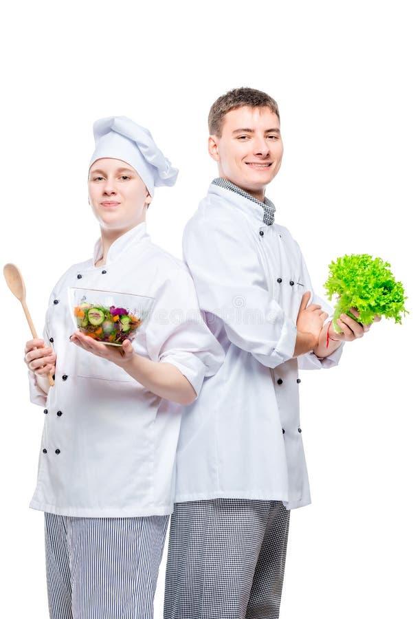 yrkesmässiga lyckliga kockar i dräkter med sallad i händer på vit bakgrund royaltyfria bilder