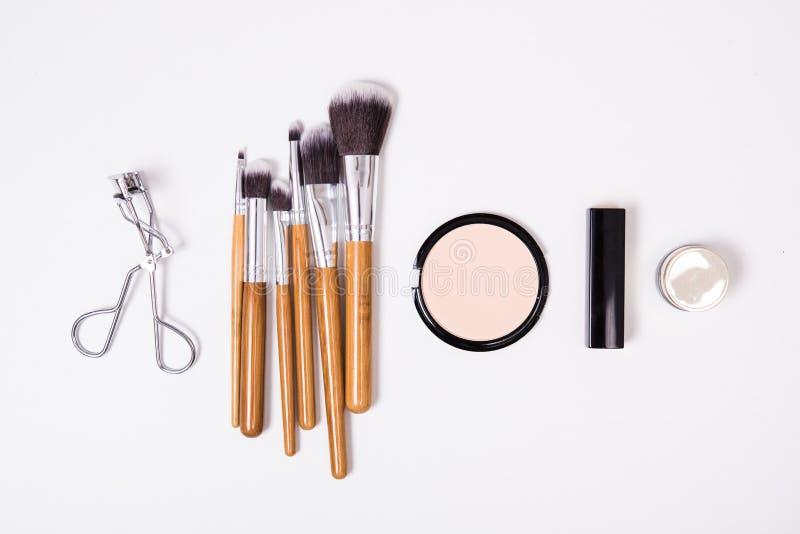 Yrkesmässiga makeuphjälpmedel som är flatlay på vit bakgrund royaltyfri foto