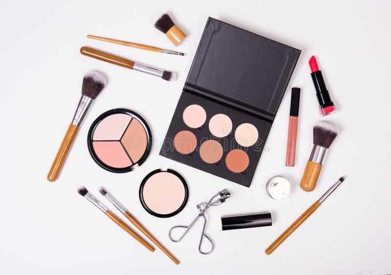 Yrkesmässiga makeuphjälpmedel som är flatlay på vit bakgrund royaltyfri bild