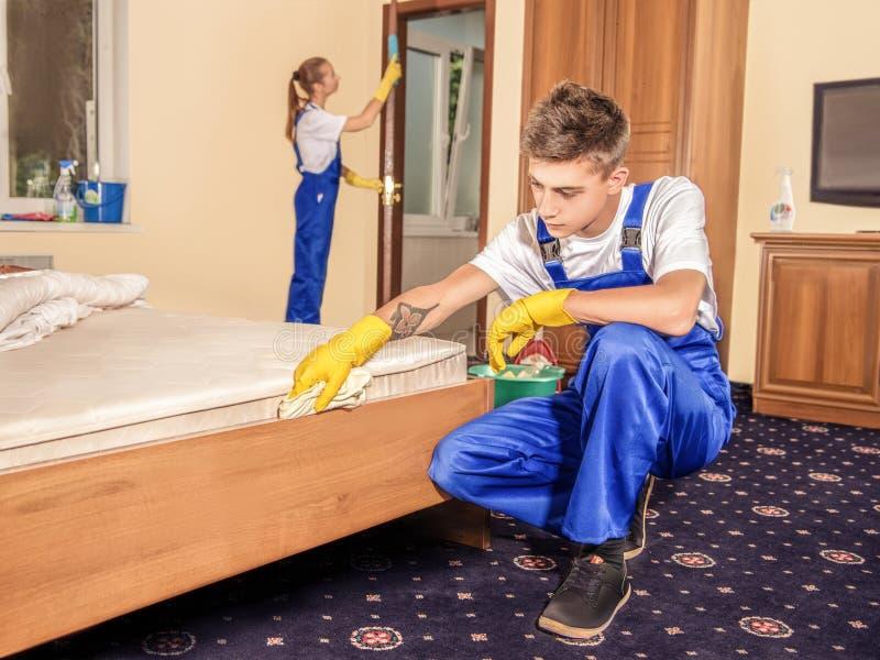 Yrkesmässiga rengöringsmedel som gör ren möblemang och golvet i rum royaltyfri foto