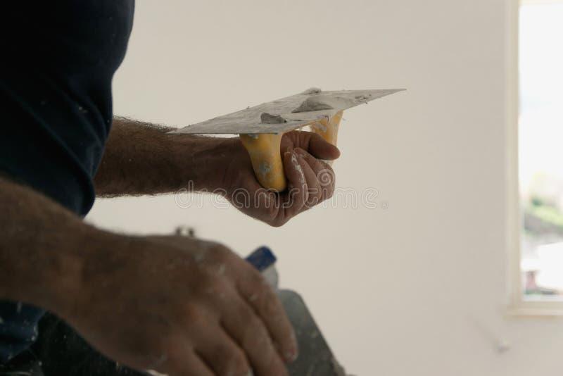 Yrkesmässiga repairmanknipahål och sprickor i väggar, constructi arkivfoton
