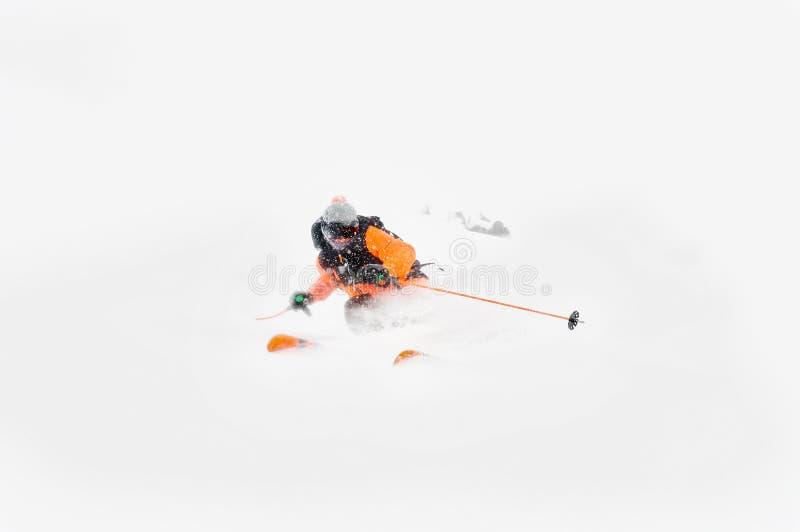 Yrkesmässiga skidåkareidrottsman nenritter ut ur djup snö, medan utföra ett skida trick i en snöstorm Vintersäsongen är royaltyfria foton