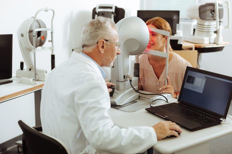 Yrkesmässigt arbeta för ögonspecialist som är hårt, medan undersöka kvinnan royaltyfri foto