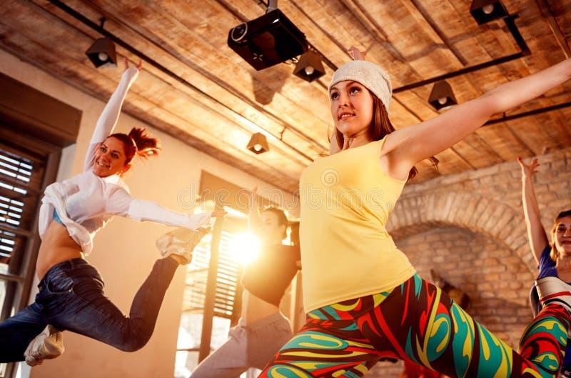 Yrkesmässigt folk som utbildar moderna danser som hoppar under musik royaltyfri foto