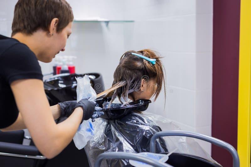Yrkesmässigt frisörfärgläggninghår av kvinnaklienten på studion royaltyfri bild