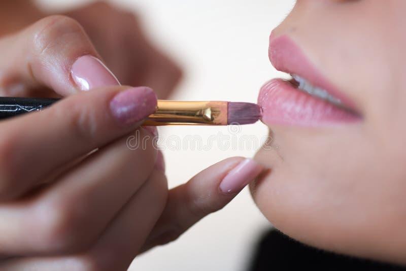 Yrkesmässigt kantsmink Lipgloss och borste arkivbild