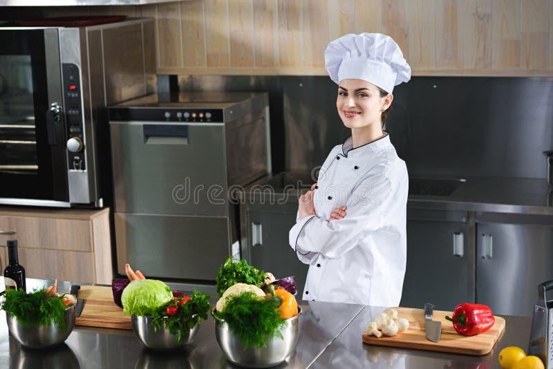 Yrkesmässigt kvinnligt kockanseende med armar vikta av tabellen arkivfoto