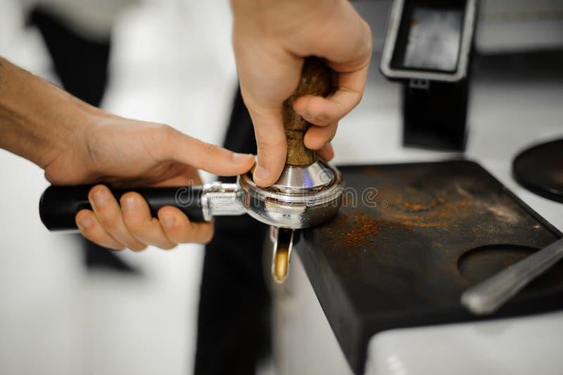 Yrkesmässigt riktigt blanda, trycka på av jordkaffe i innehavet arkivbild