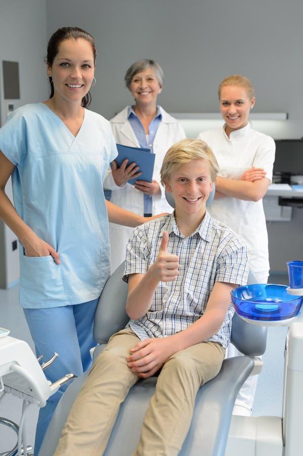 Yrkesmässigt tandläkarelag med pojkepatientthumbup royaltyfri fotografi