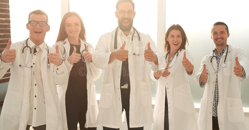 Yrkesmässigt ungt lag eller grupp av doktorer som visar upp tummar arkivfoton