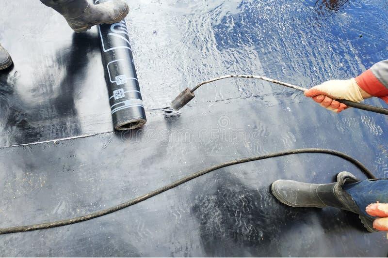 Yrkesm?ssig installation av waterproofing p? arbetaren f?r betonggrund tv? p? konstruktionsplatsen royaltyfria foton