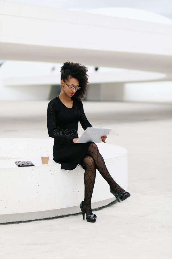 Yrkesm?ssig kvinna f?r stilfullt ungt afro h?r som anv?nder minnestavlan royaltyfria bilder