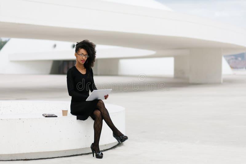 Yrkesm?ssig kvinna f?r stilfullt ungt afro h?r som anv?nder minnestavlan royaltyfri foto