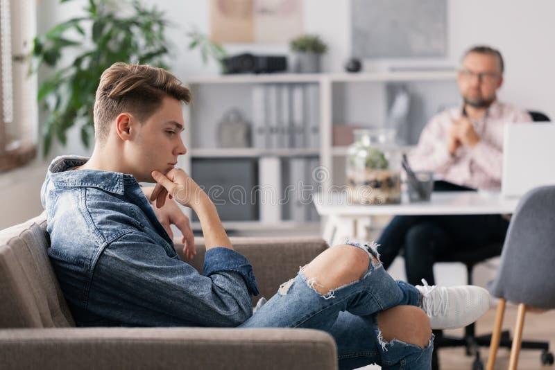 Yrkesm?ssig terapeut och ton?rs- pojke som ignorerar honom under best?mt m?te royaltyfria foton