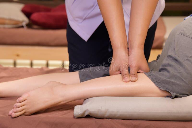 Yrkesm?ssig terapeut som ger det traditionell thai benet och kroppmassage arkivbild