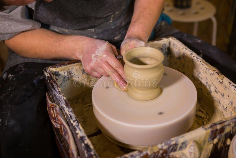 Yrkesm?ssigt forma f?r keramiker r?nar med det speciala hj?lpmedlet i krukmakeriseminarium arkivfoton