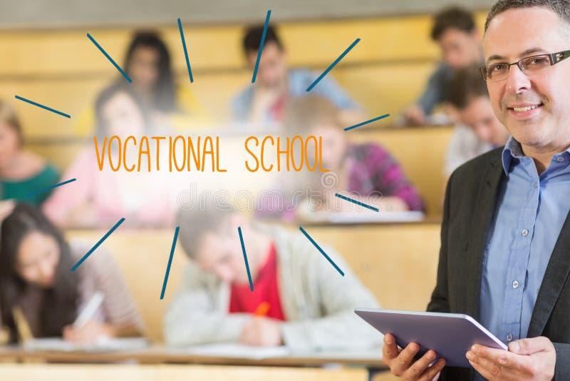 Yrkesskola mot föreläsaren som framme står av hans grupp i hörsal royaltyfria bilder