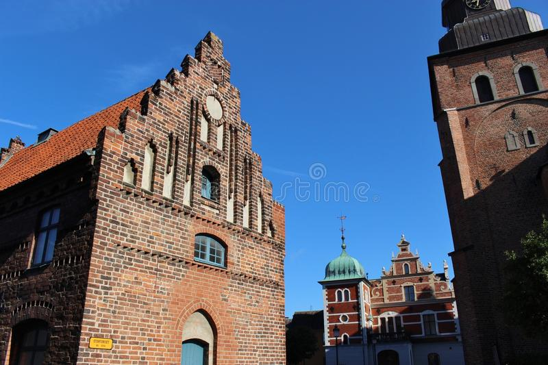 "In Ystad, South Sweden, Scandinavia, Europe. Old latin School (left) and the Roman St. Maria church (right). Ystad is film location of the crime series "" royalty free stock images"