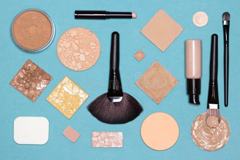 Ytbehandlar den lekmanna- uppsättningen för den korrigerande makeuplägenheten på blått arkivbild