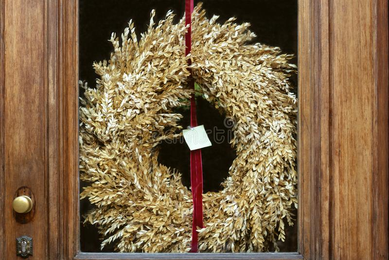 Ytterdörren har ett exponeringsglasmellanlägg och en krans av torrt gräs av guld- färg arkivfoto