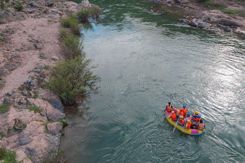 Ytterlighet som rafting på den snabba floden på en uppblåsbar gul kajak arkivfoto