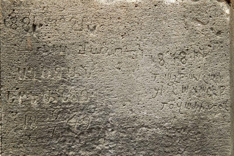 Yttersida av den forntida stenväggen med medeltida handstilar och siffror royaltyfri fotografi