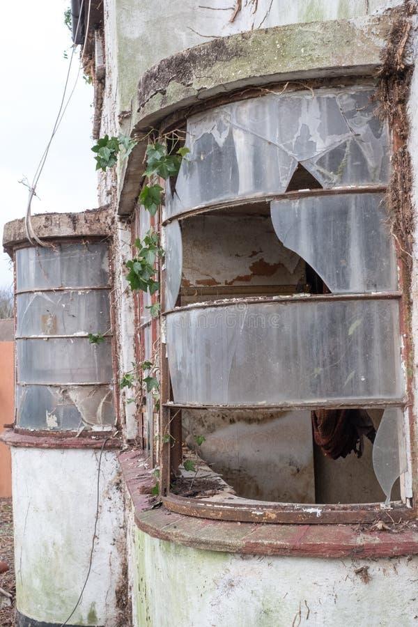 Yttersida av det övergivna huset som byggs i 30-taldecostil Huset är förfallet för rivning Harv UK royaltyfri fotografi