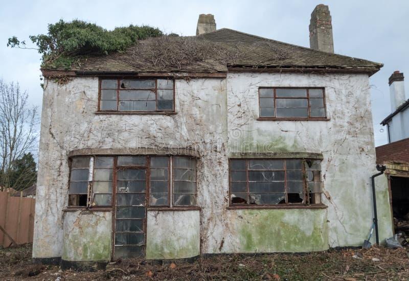 Yttersida av det övergivna huset som byggs i 30-taldecostil Huset är förfallet för rivning Rayners gränd, harv, UK royaltyfria foton